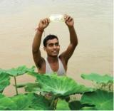 A lucky man emerges from the water with a 500 rupee note.